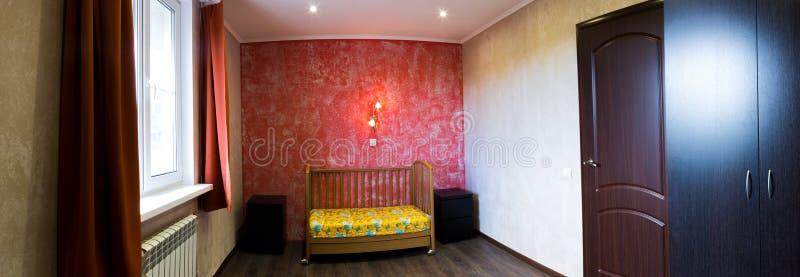 Кроватка в спальне на красной стене стоковые изображения
