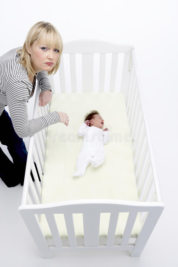 кроватка младенца смотря усиленную мать стоковое фото rf