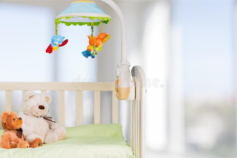 Кроватка младенца с игрушками на предпосылке окна, игровой стоковое фото rf