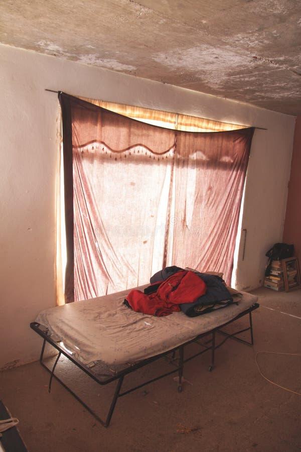 Кровать в плохом доме стоковое фото rf