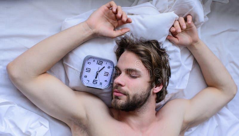 Кровать Гая расслабляющая перед звенеть будильника Самая грубая часть выходить утра просто кровати Получите вверх по рано утром стоковая фотография