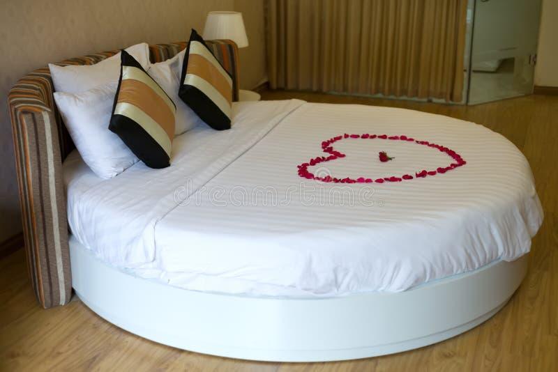 Кровать медового месяца покрынная с розовыми лепестками стоковое фото