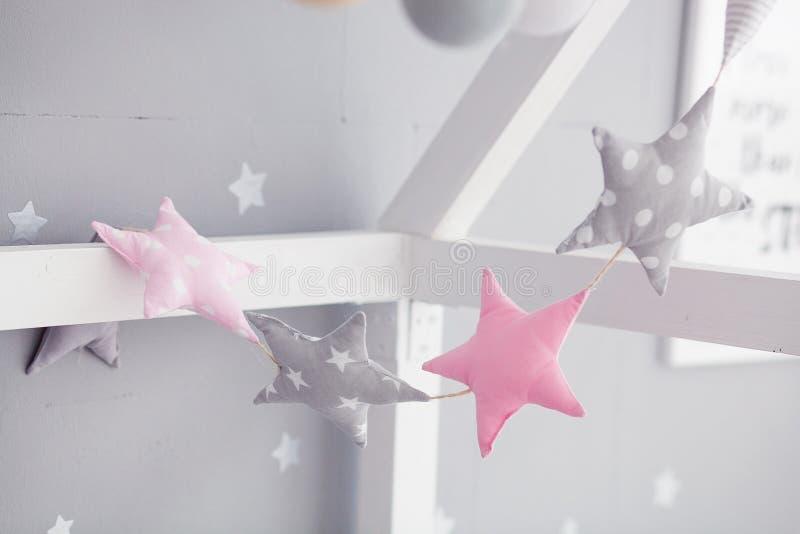 Кровать младенца с гирляндой pinwheel Розовый и серый цвет играет главные роли гирлянда в комнате ` s детей стоковая фотография