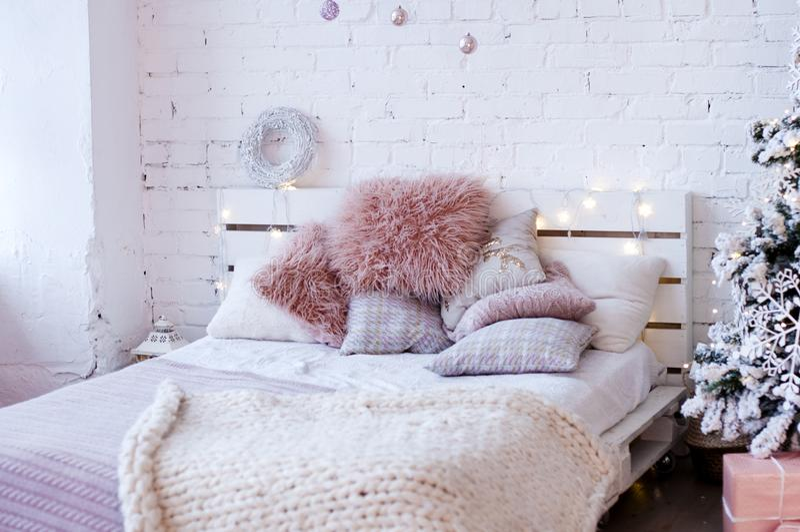 Кровать сделанная от паллетов с пушистыми розовыми подушками стоковые изображения