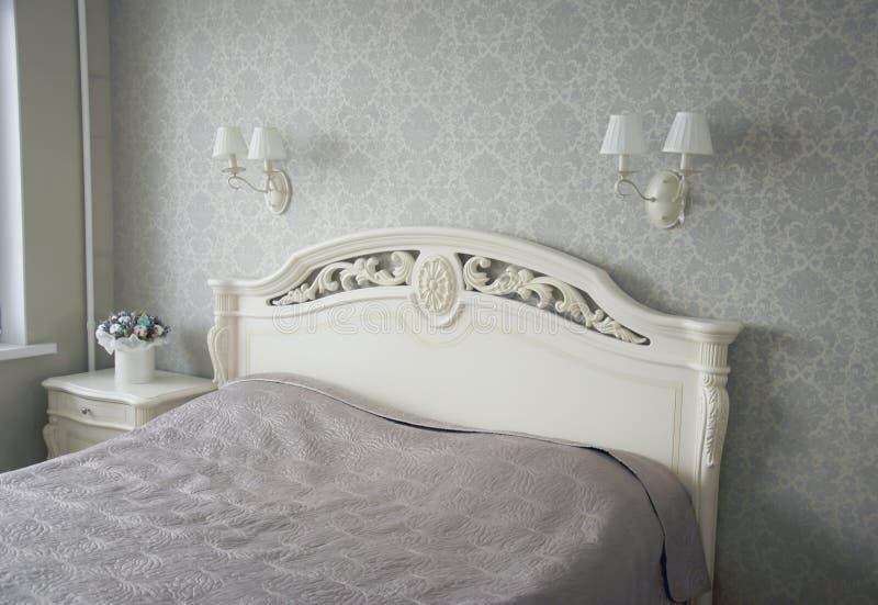 Кровать с высекаенным изголовьем в спальне Интерьер в светлом тоне стоковые фото