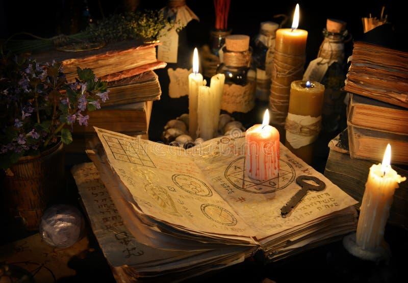 Кровопролитная свеча на книге ведьмы в свете свечи стоковая фотография