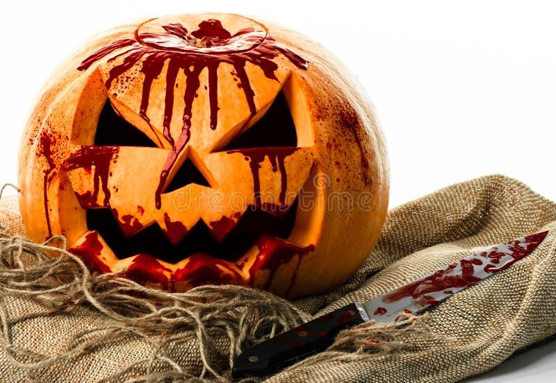 Кровопролитная тыква, фонарик jack, тыква хеллоуин, тема хеллоуина, убийца тыквы, кровопролитный нож, сумка, веревочка, белая пре стоковая фотография