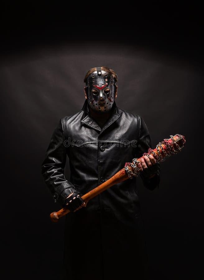 Кровопролитный маниак в маске и черном кожаном пальто стоковые фотографии rf
