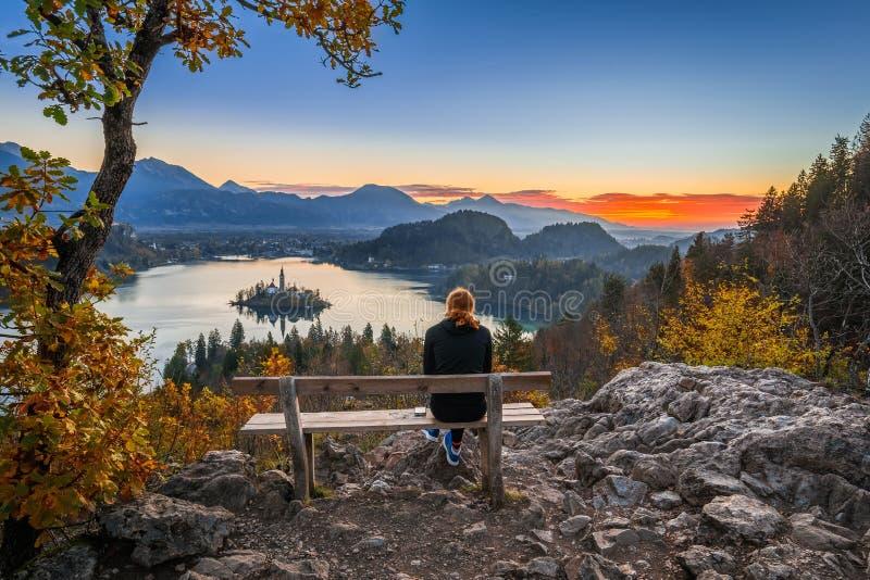 Кровоточенный, Словения - красная женщина бегуна волос ослабляя и наслаждаясь красивым взглядом осени и красочным восходом солнца стоковое фото rf