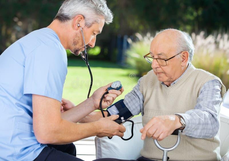 Кровяное давление доктора измеряя старшего человека стоковая фотография