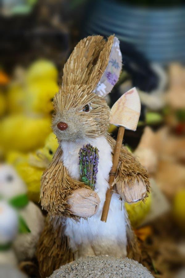 Кролик игрушки щетки бутылки с решительно взглядом на его стороне держа цветки и лопату сада с цыпленоками пасхи в предпосылке -  стоковое фото