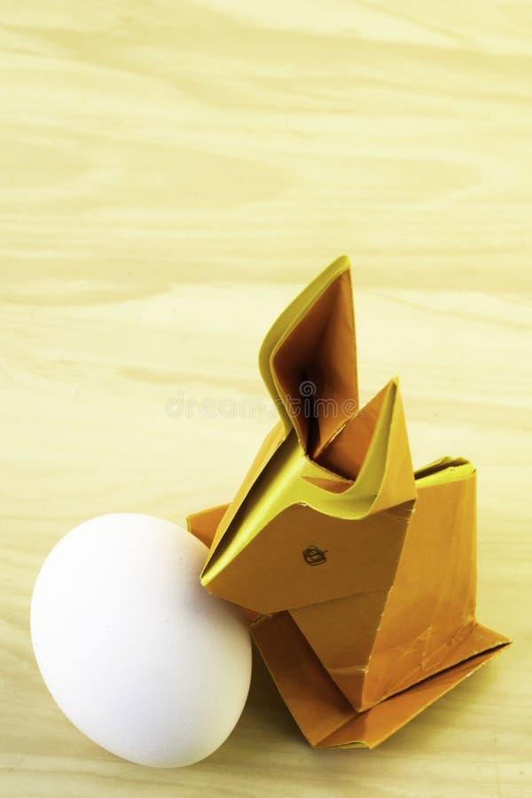 Кролик Origami от оранжевой покрашенной бумаги Зайчик пасхи и белое яйцо цыпленка на предпосылке светлого - желтый деревянный сто стоковые фотографии rf