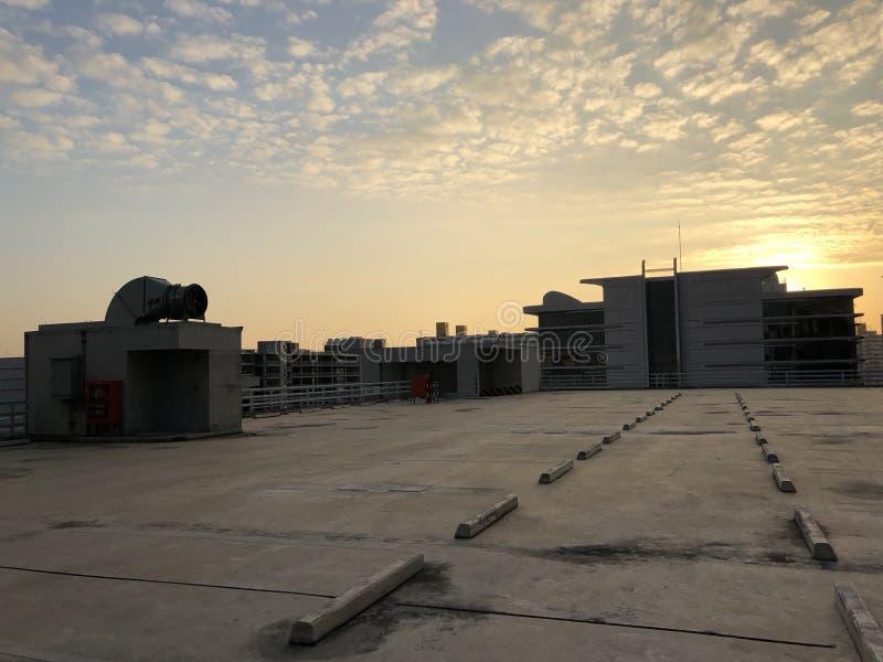 Крона автостоянки захода солнца здания теплая стоковая фотография rf