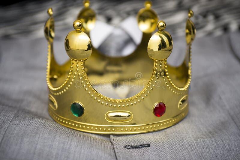 Крона золота лежа на костюме бизнесмена владение домашнего ключа принципиальной схемы дела золотистое достигая небо к метафора стоковое изображение rf