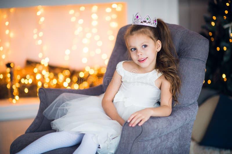 Крона счастливой жизнерадостной маленькой девочки нося возбужденная на Рожденственской ночи, сидя под украшенным загоренным дерев стоковая фотография rf
