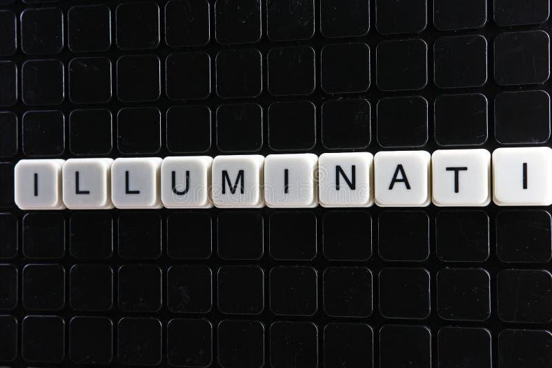 Кроссворд слова текста Illuminati Письмо алфавита преграждает предпосылку текстуры игры Белые алфавитные письма на черноте стоковая фотография