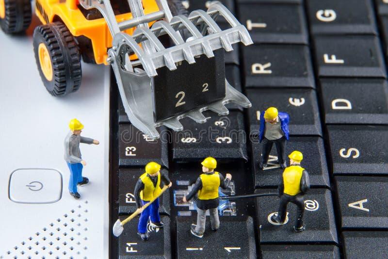 Крошечная команда игрушек инженеров ремонтируя компьтер-книжку компьютера клавиатуры C стоковая фотография rf