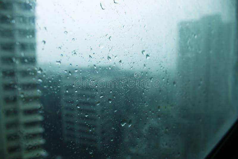 Крошечные падения воды брызгая против окна на холодном дождливом утре в городе стоковая фотография