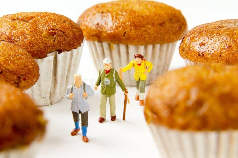 Крошечные путешественники игрушек рискуют перемещение и торт банана Еда Backgr стоковое изображение