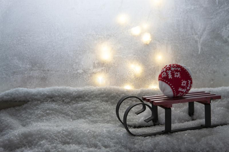 Крошечные розвальни игрушки с шариком рождества на силле окна покрытом с белым снегом Украшение зимы и рождества на открытом возд стоковое фото