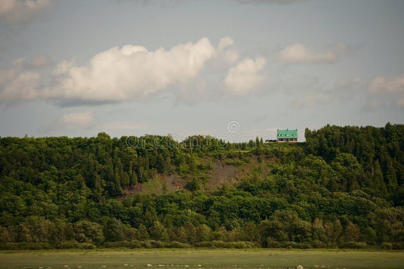 Крошечный зеленый дом на холме стоковые изображения rf