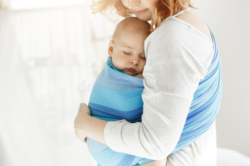 Крошечный конец новорожденного ребенка наблюдает и имеющ хороший сон в предохранении от чувства слинга младенца от его красивой м стоковые фото