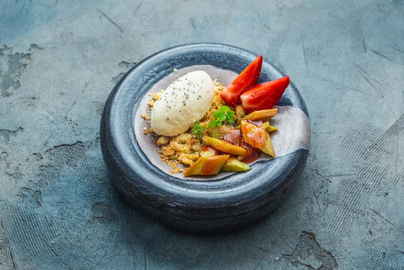 Крошите с ревенем, клубникой с ванильным мороженым r стоковые фото
