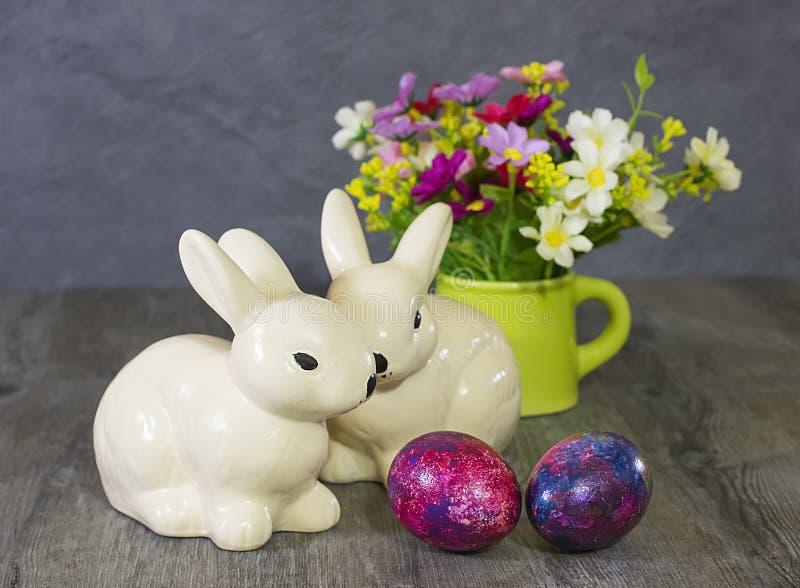 Кролики, яичка и цветки украшения пасхи стоковые изображения