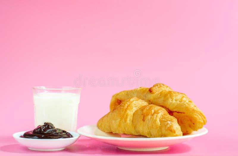 2 круассана на белых блюде и стекле парного молока на розовой задней земле с космосом экземпляра для вашего текста Концепция завт стоковые фото