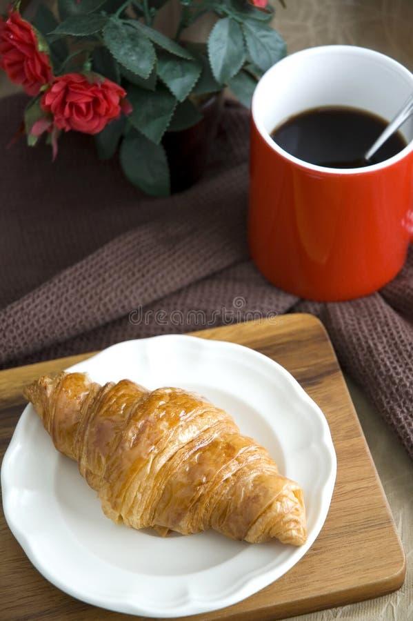 Круассан, который служат на блюде с кофе стоковое изображение