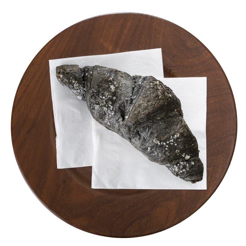 Круассан угля, на белом serviette и деревянной плите, изолированных на белизне Черный цвет должный к углероду овоща aka стоковое фото