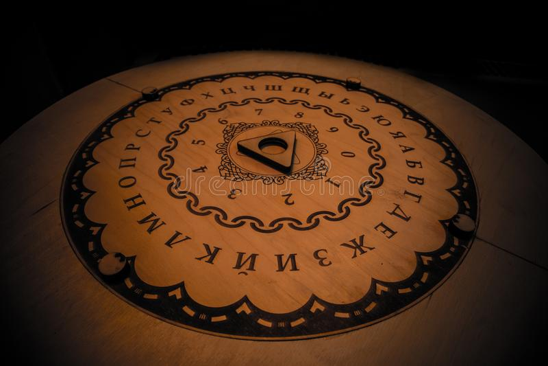 Круглая говоря духовные доска и planchette используемые на seances для связывать с духами, призраками и смертельно Русские характ стоковое фото rf
