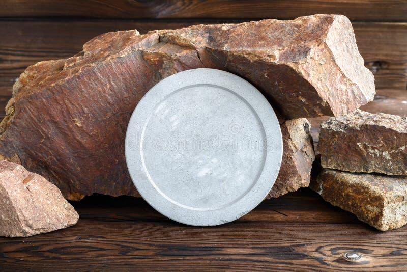 Круглая конкретная плита на предпосылке камней гранита Деревянная предпосылка стоковое фото rf