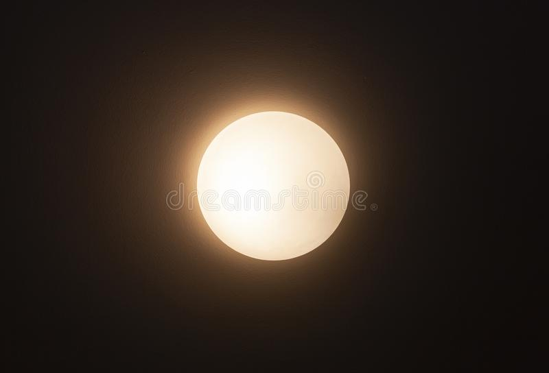 Круглая лампа sconce накаляет над темной стеной стоковые фото