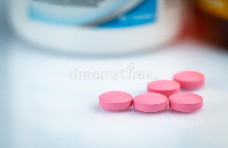 Круглая розовая таблетка планшетов на запачканной бутылке лекарства Витамины и минералы плюс витамин e фолиевой кислоты и цинк в  стоковое изображение rf
