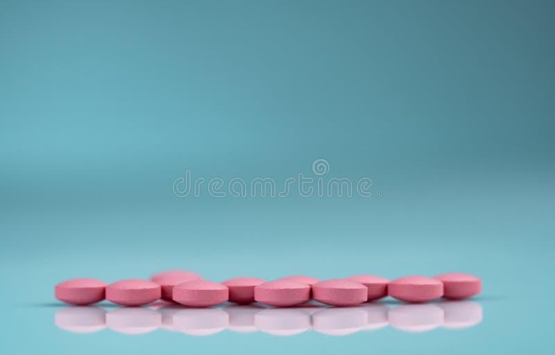 Круглая розовая таблетка планшетов на предпосылке градиента Витамины и минералы плюс витамин e фолиевой кислоты и цинк в бутылке  стоковое изображение rf