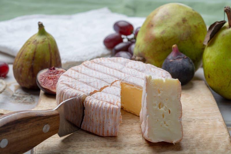 Круглая часть французского румян Fleur сыра сделанного из молока коровы, который служат как десерт со свежими смоквами и грушами стоковые изображения