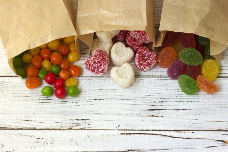 Круглые покрашенные конфета и мармелад в бумажном мешке на деревянном столе, яркие помадки, белая предпосылка стоковое изображение