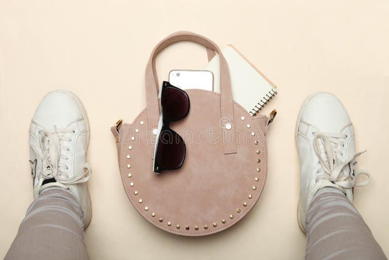 Круглые сумка, смартфон, солнечные очки и ноги женщин в тапках спорт стоковая фотография