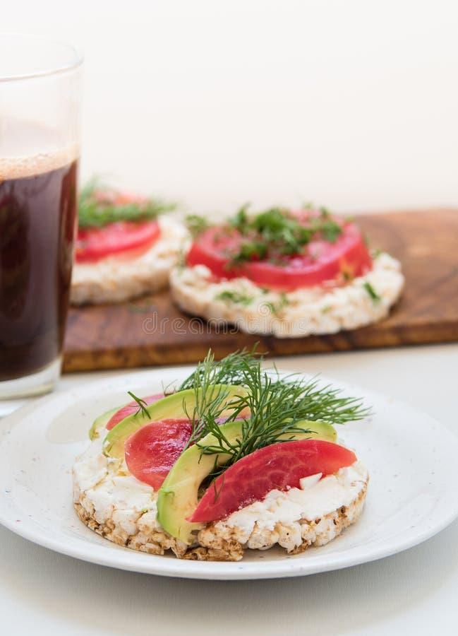 Круглые хрустящие хлебы с сыром, томатами и авокадоом стоковые изображения