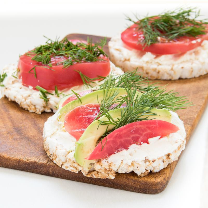 Круглые хрустящие хлебы с сыром, томатами и авокадоом стоковое изображение