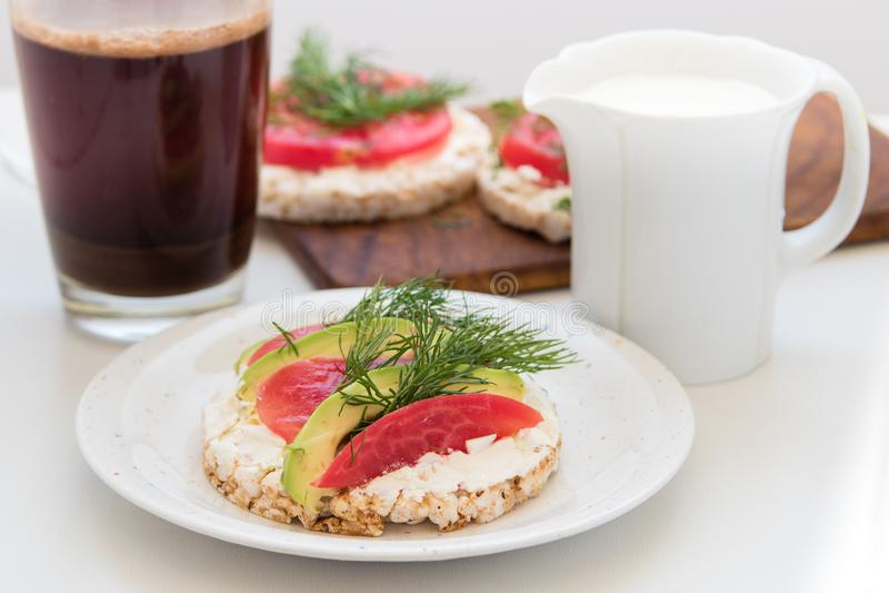 Круглые хрустящие хлебы с сыром, томатами и авокадоом стоковое фото rf