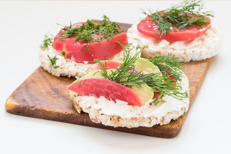 Круглые хрустящие хлебы с сыром, томатами и авокадоом стоковая фотография