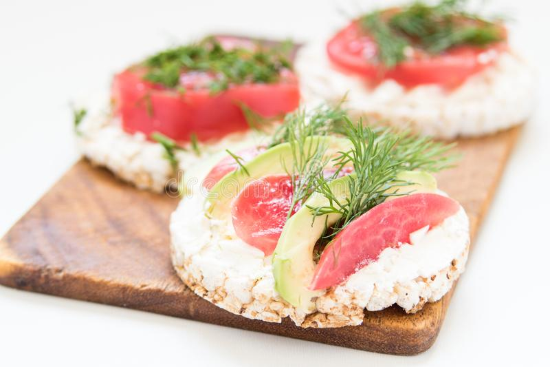Круглые хрустящие хлебы с сыром, томатами и авокадоом стоковое изображение rf