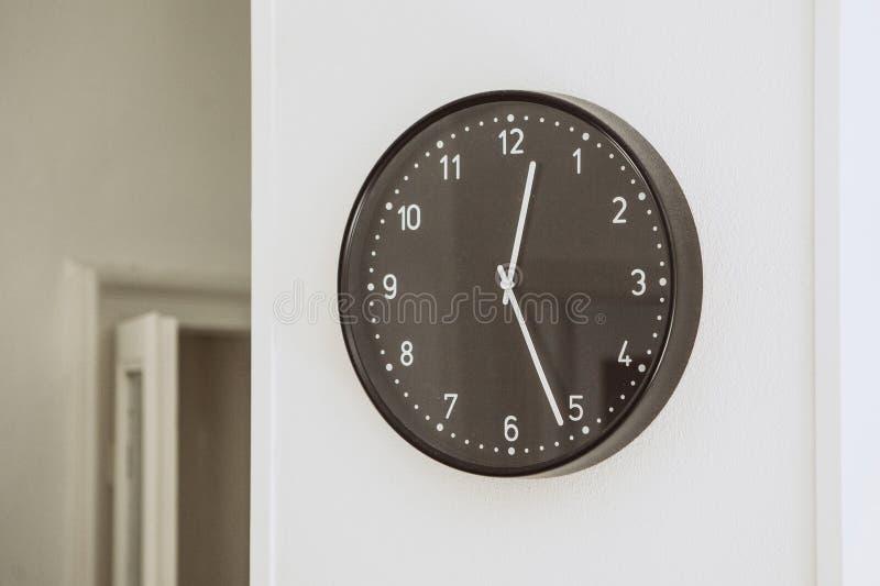 Круглые черные часы на белой стене стоковые изображения