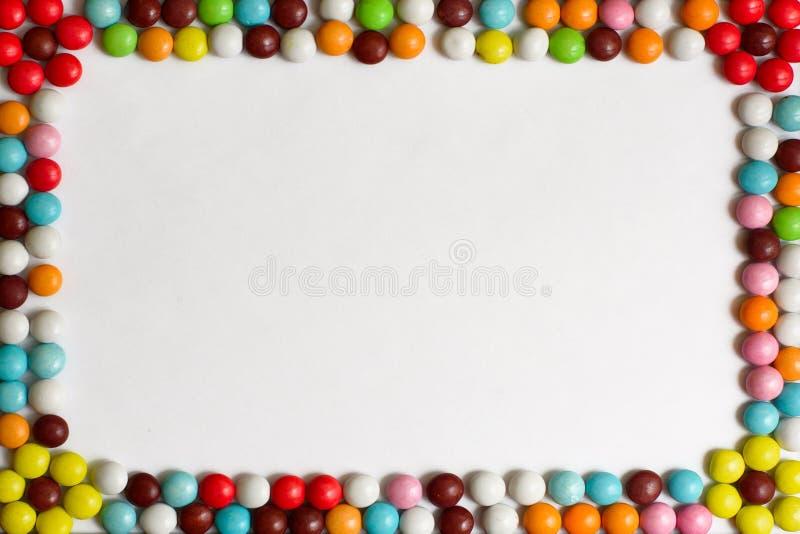 Круглые Bonbons шоколада покрытые с покрашенной поливой на белой предпосылке Взгляд сверху скопируйте космос стоковые фото