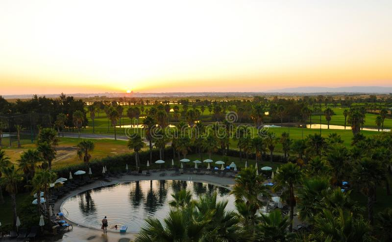 Круглый бассейн и красивые пейзаж захода солнца, поле для гольфа, небольшие озера и деревья, праздники семьи стоковое фото