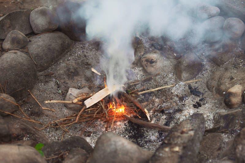 Круглый каменный камин леса с золой угля и древесины Лагерь стойки леса охотников и туристов Дым от лагерного костера стоковые изображения rf