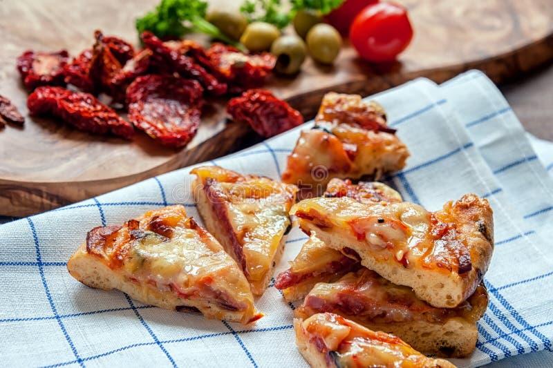 Круглый отрезок Маргариты пиццы сосиски в части для того чтобы подать ткань с солнц-высушенными томатами Селективный фокус стоковые фото