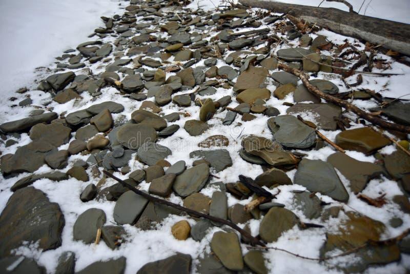 Круглый плоский камень выступая через снег стоковое изображение
